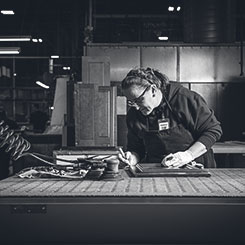 An Omega production associate working on the detailing of a cabinet door