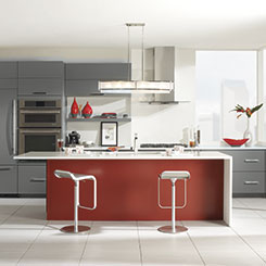 Contemporary kitchen design with Vail cabinets in gray with a red island