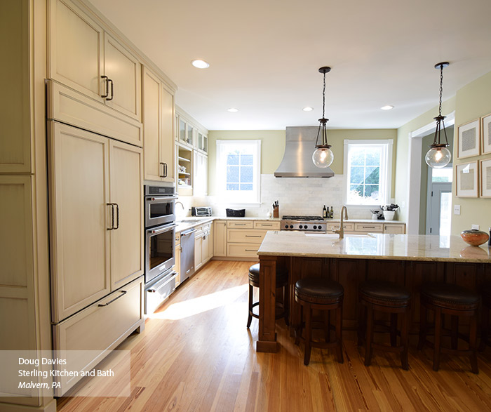 Casual kitchen with off white glazed cabinets and a dark kitchen island
